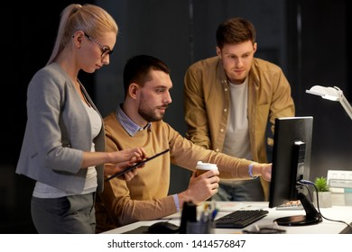 business, deadline and technology concept - coworkers with computer and takeout coffee working late at night office