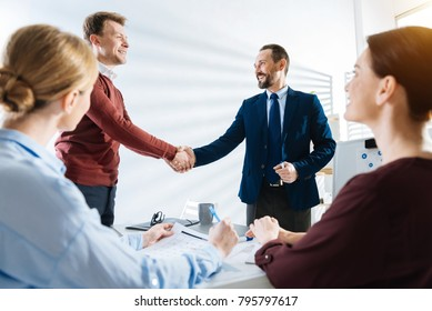 Business deal. Attractive handsome two male colleagues shaking hands while congratulating each other and standing