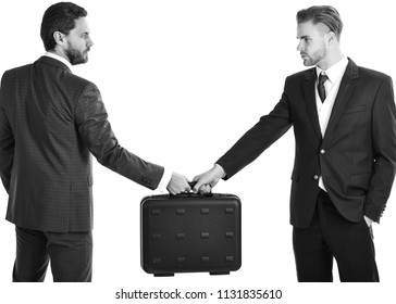 Business deal between businessmen in suits. Businessmen with serious faces hold briefcase. Business exchange concept. Handover of suitcase with bribe in hands of partners, isolated on white background