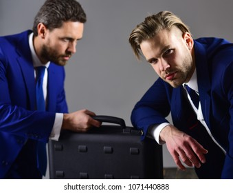 Business deal concept. Businessmen with black briefcase on dark background. Men in suit or business partners with serious faces meet for deal. Handover of briefcase with illegal goods or bribe.