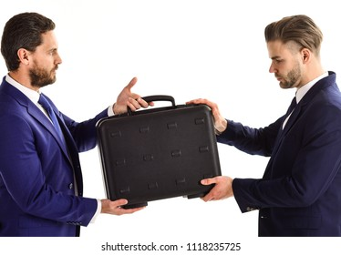 Business and deal concept. Businessmen with serious faces hold black briefcase. Handover of suitcase in hands of partners on white background. Business exchange between businessmen in classic suits.