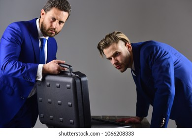 Business deal concept. Handover of briefcase with illegal goods. Men in suit or business partners with suspicious faces meet for deal. Businessmen with opened briefcase on dark background.