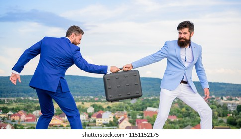 Business deal landscape background. Businessman takes away briefcase from business partner. Fraud and extortion concept. Man cheating while handover meeting. Men in suits handover briefcase.