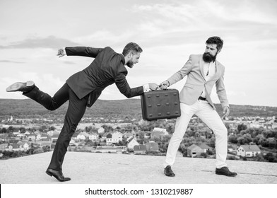 Business deal landscape background. Businessman takes away briefcase from business partner. Fraud and extortion concept. Men suits handover briefcase. Rascal racketeer extortionist cheating handover.