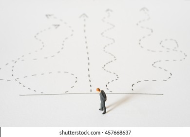 Business decision concept. Businessman standing confusing with arrow pathway choice.