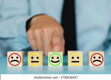 Business decision concept. Hand arranging symbol with smiley face icon on wood cube block.Business service rating, Satisfaction concept.