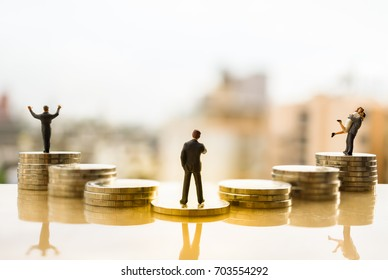 Business decision concept. Miniature people: Businessman standing in front of coin stack pathway choice for family life or success.