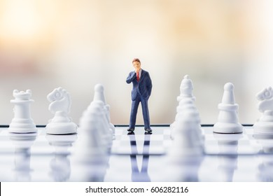 Business decision making concept. Miniature people : small businessman figure standing and walking on chessboard with chess pieces