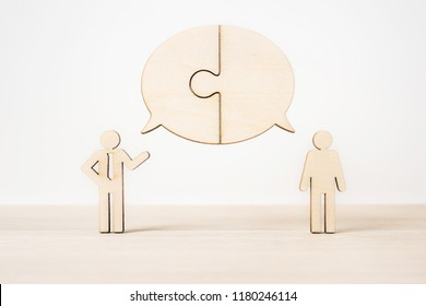 Business and design concept - group of wooden businessman icon with jigsaw dialogue frame on wooden desktop and white background. it's discussion, leadership concept