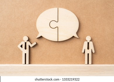 Business and design concept - group of wooden businessman icon with jigsaw dialogue frame on kraft paper. it's conversation, leadership concept
