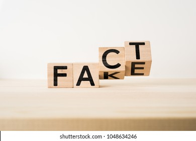 """Business and design concept - surreal abstract geometric wooden cube take by hand with word """" FACT & FAKE """" concept on wood floor and white background"""