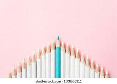Business and design concept - lot of white pencils and one color pencil on pink paper background. It's symbol of leadership, teamwork, success and unique.