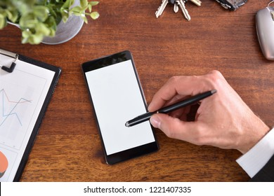 Business desk with hand interacting on a mobile phone with active capacitive stylus. Horizontal composition. Top view