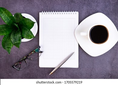 Business desk with office supplies, notebook, pen, flower, glasses on a dark background. Flat design, view from the top. Concept.