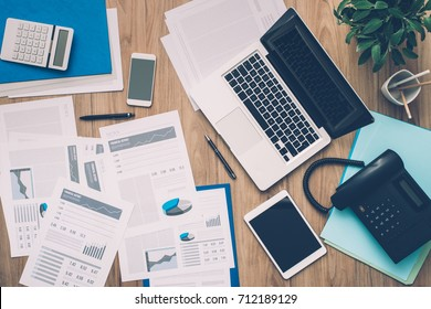 Business desktop with laptop, tablet, calculator and financial reports, top view