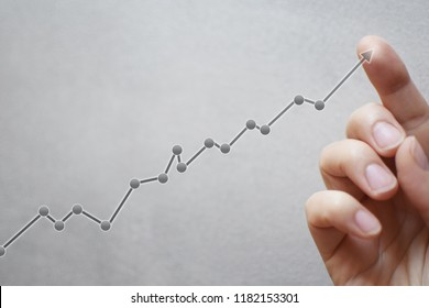 Business development and long term growing up revenue concept. Finger touching transparent arrow graph growth or increase business chart on light grey  background with copy space for text or image.