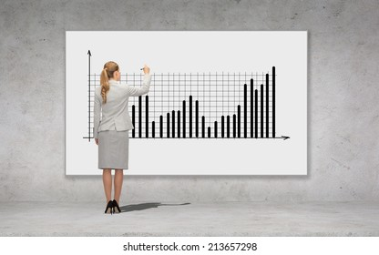 business, development and office people concept - businesswoman with marker drawing chart over concrete wall background from back