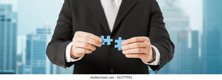 business, development and people concept - close up of man trying to connect puzzle pieces over city background