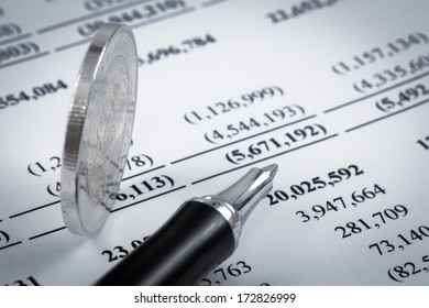 Business diagram on financial report with coins and pen