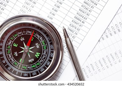 Business direction. Closeup of compass near pen on paper with digits