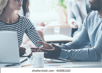 Business discussion. Close-up of two young business people discussing something while sitting at the office desk together while their colleagues sitting in the background