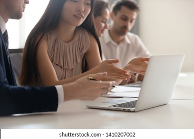 Business discussion concept, asian female employee talking to male colleague pointing at laptop discuss online work solve problem using corporate software doing research on computer at office meeting