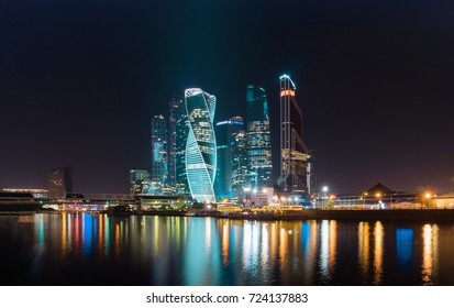Business district of the city in colorful night lights. Midnight lights of a big city are reflected in the river