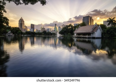Business district cityscape from a park with twilight time from lumpini park, Bangkok Thailand. The sky is burst.
