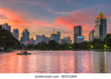 Business district cityscape from a park with Twilight Time from Lumpini Park, Bangkok, Thailand