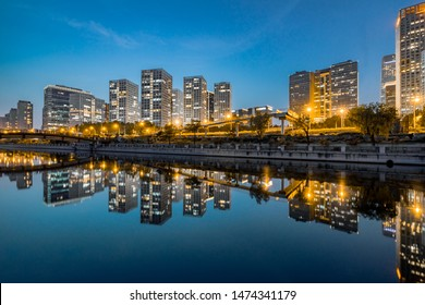 Business district office buildings and water reflection in Beijing at night