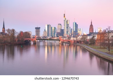 Business district with skyscrapers and mirror reflections in the river at pink sunrise, Frankfurt am Main, Germany