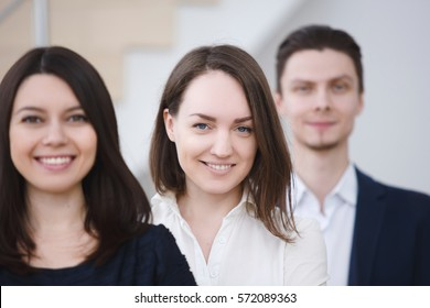 Business diversity team. Young attractive woman with happy colleague on background. Group portrait of StartUp or small business.