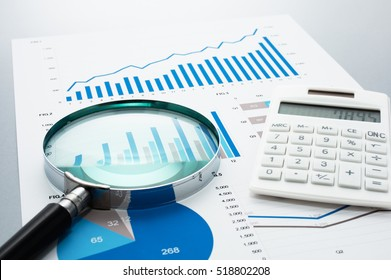 Business document, magnifying glass, and calculator on gray reflection background. Many graphs and charts. Concept image of data reviewing.
