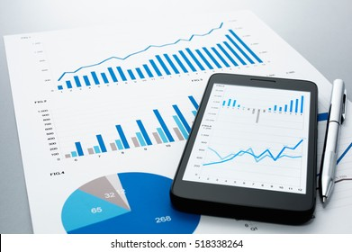 Business document, smart phone and pen on gray reflection background. Many graphs and charts. Concept image of data gathering.