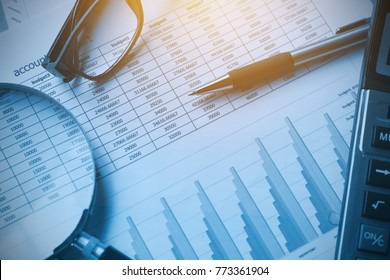 business documents accounting with calculator, pen, glasses and magnifying glass. concept for financial