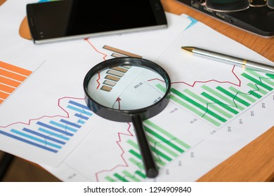 Business documents with charts growth, magnifier search and pen. Workplace businessman.