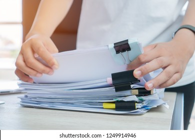 Business Documents concept : Businessman hands working in Stacks paper files for searching and checking unfinished document achieves with clip papers on busy work desk office. Soft focus