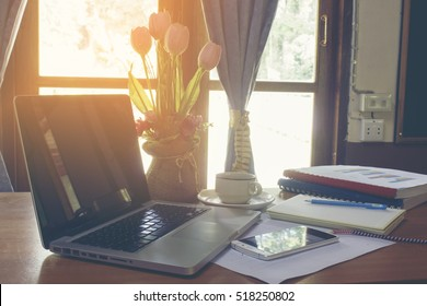 Business documents with laptop on desk.