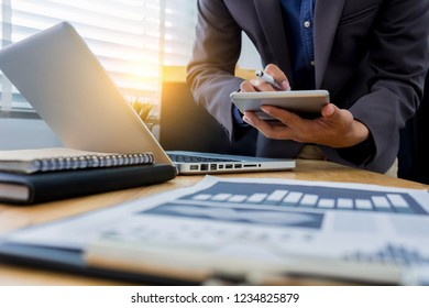 business documents on office desk with laptop and smart phone and graph business diagram and man working at office.