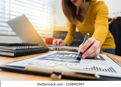 business documents on office desk with laptop and smart phone and graph business diagram and women working at office .
