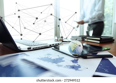 business documents on office table with texture the world on digital tablet and man using smart phone  in the background Elements of this image furnished by NASA