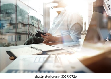 business documents on office table with smart phone and digital tablet and graph diagram and man working in the background