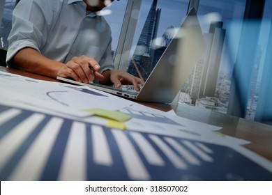 business documents on office table with smart phone and laptop computer and graph finance with social network diagram and man working in the background