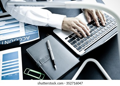 business documents on office table with laptop computer and graph business diagram