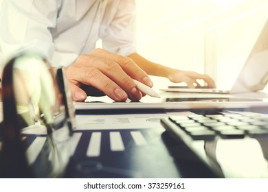 business documents on office table with laptop computer and graph finance digital diagram and businessman working in the background