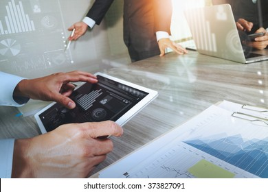 business documents on office table with smart phone and laptop computer and digital graph finance with social network diagram and three colleagues discussing data in the background