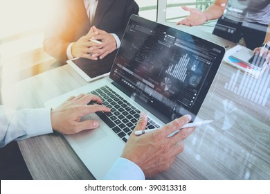 business documents on office table with smart phone and laptop computer and graph financial with social network diagram and three colleagues discussing data in the background   - Shutterstock ID 390313318