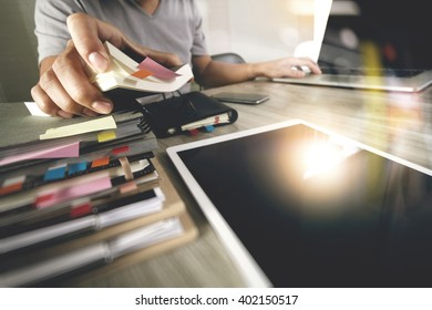 business documents on office table with smart phone and digital tablet and graph finance with stack book and man working in the background