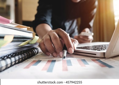 business documents on office table with smart phone and digital tablet and graph financial with social network diagram and man working in morning light
