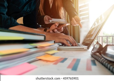 business documents on office table with tablet, smart phone and laptop and two colleagues discussing data in the background in morning light